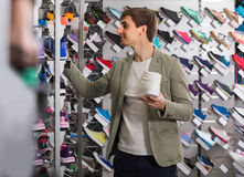 Young man choosing shoes in the sport store. Cheerful young american man choosing shoes in the sport store Stock Image