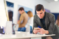 Young man choosing smart phone in the store stock photography