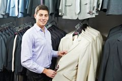 Young man choosing suit in clothes store. Young man choosing suit jacket during apparel shopping at clothing store Royalty Free Stock Photography