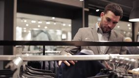 Young man choosing suit in clothing store or mall. Sale, shopping, fashion, style and people concept - elegant young man in suit choosing clothes in mall or stock video footage