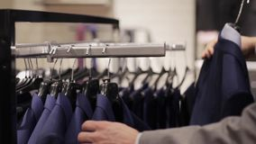 Young man choosing suit in clothing store or mall stock video