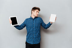 Young man choosing between tablet computer and book. Image of young man standing over grey wall and choosing between tablet computer and book. Looking aside Royalty Free Stock Photography