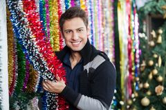 Young Man Choosing Tinsels At Store Royalty Free Stock Image