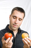 Young man choosing between tomato and peach Stock Photography