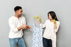 Young man choosing between two woman`s dresses. Young cheerful men choosing between two woman`s dresses isolated stock photo