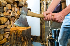 Young man chopping fire wood in mountain chalet Stock Image