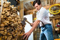 Young man chopping fire wood in mountain chalet Royalty Free Stock Images