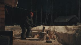 Young man chopping wood in the yard. Winter evening. Wide shot. 4K stock footage