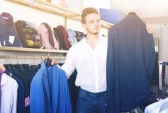 Young man chousing jacket Royalty Free Stock Image