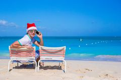 Young man in Christmas hat at beach chair Royalty Free Stock Image
