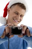 Young man with christmas hat and camera Stock Image