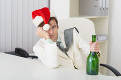 Young man in christmas hat cap with bottle Royalty Free Stock Image