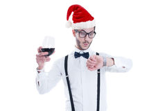 Young man with Christmas hat is looking at his watch Royalty Free Stock Images