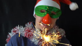 Young man in Christmas hat and mask holding a burning Sparkler stock video footage