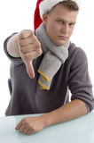 Young man with christmas hat showing thumb down Royalty Free Stock Image