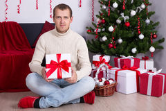 Young man with christmas present boxes under christmas tree Stock Images