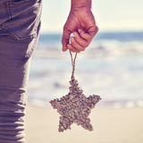 Young man with a christmas star on the beach, filtered Stock Image