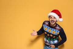 Young man in Christmas sweater and hat on color background. Space for text royalty free stock images