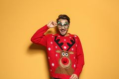 Young man in Christmas sweater with party glasses. On color background royalty free stock images