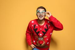Young man in Christmas sweater with party glasses. On color background royalty free stock photography