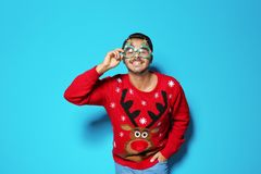 Young man in Christmas sweater with party glasses. On color background royalty free stock photo
