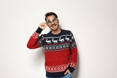 Young man in Christmas sweater with party glasses. On white background royalty free stock photography