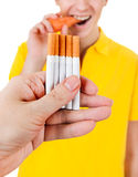 Young Man and Cigarettes. Young Man with Carrot refuse a Cigarette Isolated on the White Background Stock Photos