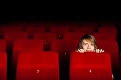 Young man in the cinema hiding behind a chair. Watching scary movie Royalty Free Stock Images