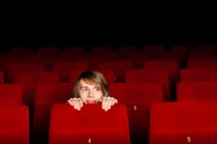 Young man in the cinema hiding behind a chair Royalty Free Stock Photos