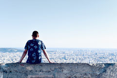 Young man with the city bellow him. A young caucasian man, seen from behind, sitting at the top of a hill observing the city below him Royalty Free Stock Photo
