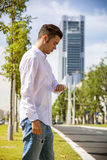 Young man in city looking at wrist watch Royalty Free Stock Photography