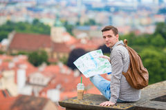 Young man with a city map and backpack background european city. Caucasian tourist looking at the map of European city. Happy young man with a city map and a Stock Photos