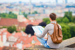 Young man with a city map and backpack background european city. Caucasian tourist looking at the map of European city Stock Images