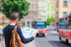 Young man with a city map and backpack in Europe. Caucasian tourist looking at the map of European city in search of Royalty Free Stock Images