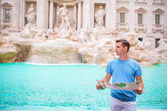 Young man with city map iat Trevi Fountain, Rome. Travel tourist guy on holidays in Europe. Royalty Free Stock Photos