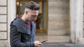 Young man in city, walking and talking with someone on smartphone