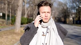 Young man in city, walking and talking with someone on smartphone. Young blue eyed man in city park, using smartphone to call someone while walking stock video footage