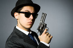 Young man in classic striped costume holding gun Stock Images