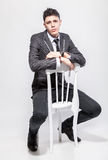 Young man in classic suit sitting on white wooden chair at studi Stock Images