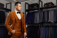 Young man in classic vest against row of suits in shop. Businessman in classic vest against row of suits in shop. A young stylish man in a jacket. It is in the Stock Photography