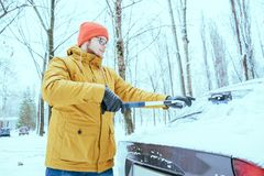 Young man clean car after snow storm stock images