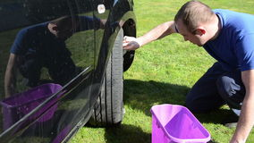 Young man clean wash his favourite car wheel with soap on grass stock video