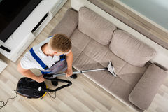 Young Man Cleaner Sofa With Vacuum Cleaner Royalty Free Stock Image