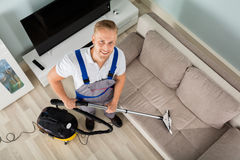 Young Man Cleaner Sofa With Vacuum Cleaner. High Angle View Of A Young Man Cleaning Floor With Vacuum Cleaner Royalty Free Stock Photos