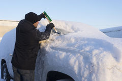 Young man cleaning car from snow Royalty Free Stock Image