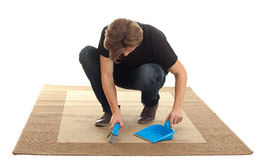 Young man cleaning carpet Stock Images