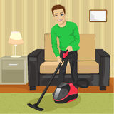 Young man cleaning carpet with vacuum cleaner at home Stock Photo