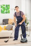Young man cleaning carpet with vacuum cleaner. In living room Stock Photos