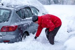 Man is cleaning clean off his car of snow cover by brush. Snow covered car. Young Man is cleaning clean off his car of snow cover by brush. Snow covered car stock image
