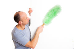 Young man cleaning with feather duster Stock Photography